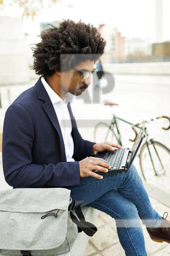 Spain, Barcelona, businessman with bicycle in the city sitting on bench using laptop