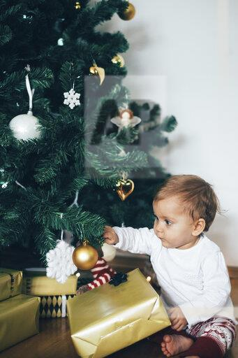 Baby girl sitting on the floor playing with Christmas decoration