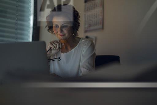 Businesswoman working overtime, using laptop, holding glasses