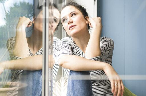 Serious woman looking out of window at home