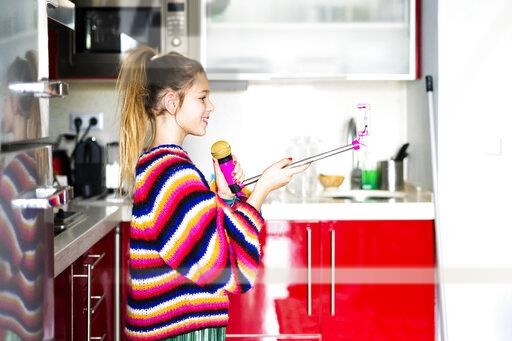Girl playing with microphone and smartphone in kitchen at home