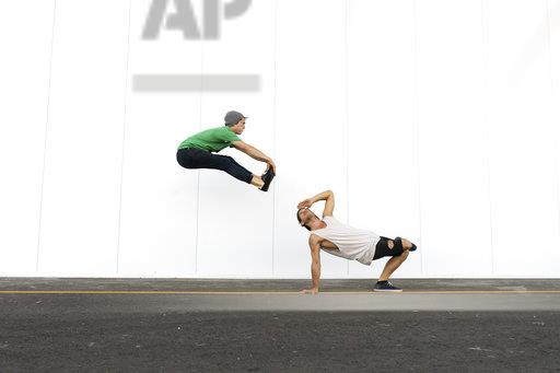 Two acrobats doing tricks together, jumping mid-air