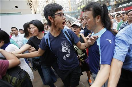 A pro-democracy student protester argues with angry locals trying to remove the barricades blocking streets in Causeway Bay, Hong Kong, Friday, Oct. 3, 2014. Hong Kong protest leaders on Friday welcomed an offer by the territory's leader of talks to defuse the crisis over demonstrations seeking democratic reforms, though they continued to demand he resign and maintained barricades around government headquarters, frustrating staff going to work.