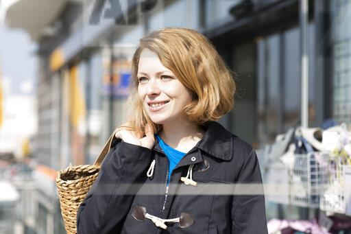Portrait of smiling woman with shopping bag in front of supermarket