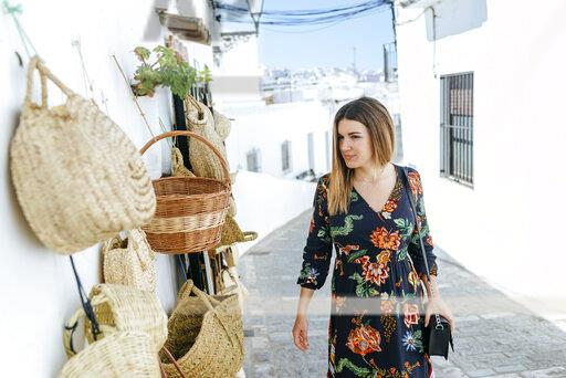 Spain, Cadiz, Vejer de la Frontera, fashionable woman looking at bags and baskets at a shop