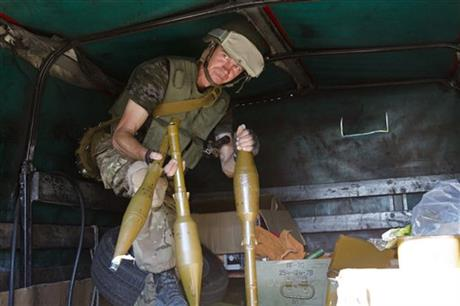 A Ukrainian volunteer of Donbas Battalion holds up weapons captured from rebels in the city of Lisichansk, Luhansk region, eastern Ukraine Saturday, July 26, 2014. Volunteers from the Donbas Battalion, a volunteer militia for a united Ukraine, told The Associated Press their units, along with the Ukrainian army, regained control of Lisichansk on Friday. (AP Photo/Dmitry Lovetsky)