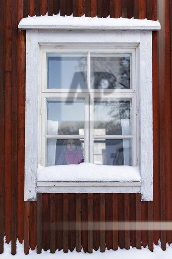 Finland, Kuopio, little girl looking out of window of farmhouse in winter