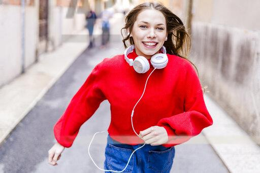 Young woman wearing red pullover, running