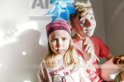 Portrait of boy and little sister made up for carnival
