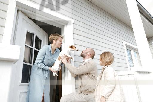 Happy family with dog on porch of their house