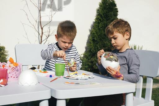Friends painting Easter eggs in garden