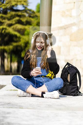 Young woman using smartphone and headphones in Verona