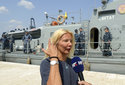 In this photo taken Aug. 19, 2018, a woman who identified herself as Kay from England, is interviewed by local media in front of a Croatian Coast Guard vessel in the port in Pula, Croatia. A British woman was rescued Sunday after falling from a cruise ship and spending 10 hours in the Adriatic Sea at night, Croatia's coast guard said. (AP Photo)