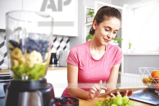 Portrait of smiling young woman using tablet in the kitchen