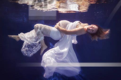 Pregnant woman wearing white dress under water