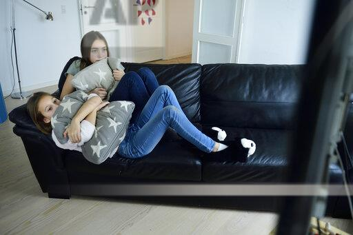 Two sisters watching television on couch