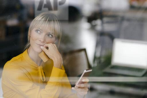 Blond businesswoman sitting at window, doing a paymant with smartphone and creditcard