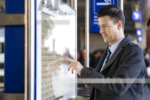 Businessman checking departures board at the train station