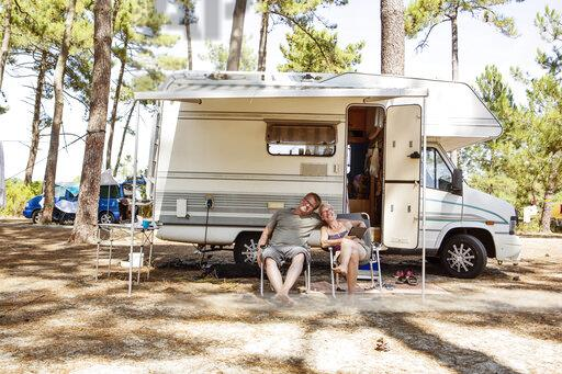 France, Gironde, happy couple sitting in front of camper on camping ground