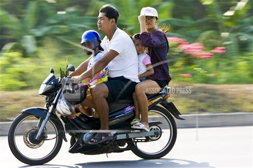 Creative Robert Harding Productions /AP Images A   Thailand 1161-2807 Family travel on a motorcyle, Bangkok, Thailand