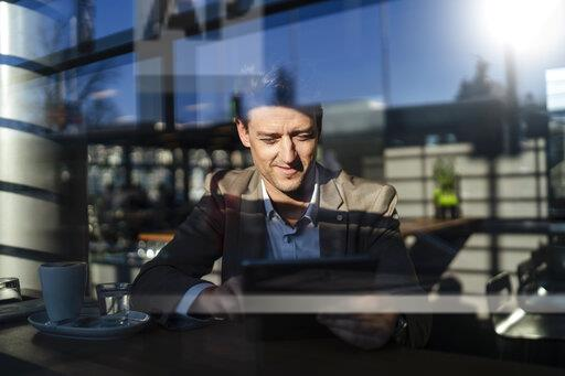 Businessman using tablet behind the window in a cafe