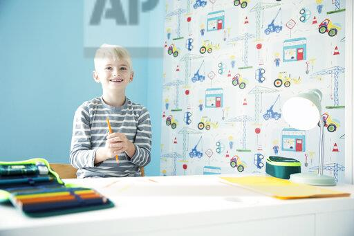 Smiling boy doing homework at desk in children's room