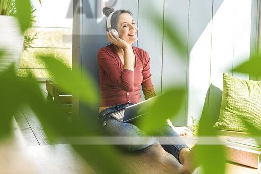 Happy woman with headphones and laptop sitting at the window at home