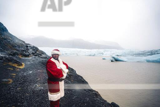 Iceland, smiling Santa Claus standing in front of glacier