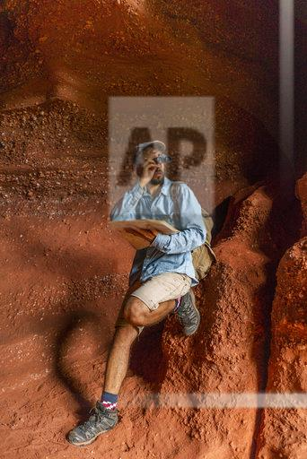 Young man sitting in a cave, looking through binoculars, holding map