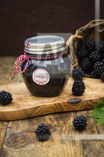 Glass of homemade blackberry jelly and blackberries on wood