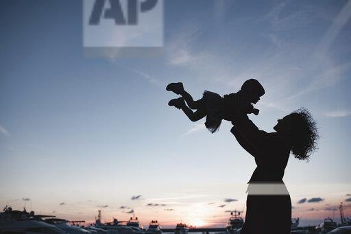 Silhouette of mother playing with her daughter at sunset