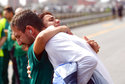 People hug during a moment of silence commemorating the victims of a highway bridge collapsed a month ago, in Genoa, Italy, Friday, Sept. 14, 2018. At 11.36 a.m. local time (0936 GMT), the city marked the moment a month ago when the Morandi bridge collapsed, plunging dozens of vehicles into a dry riverbed. (Luca Zennaro/ANSA via AP)