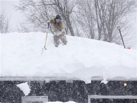 Tom Mudd clears snow from the roof of his house on Thursday, Nov. 20, 2014, in Cheektowaga, N.Y.