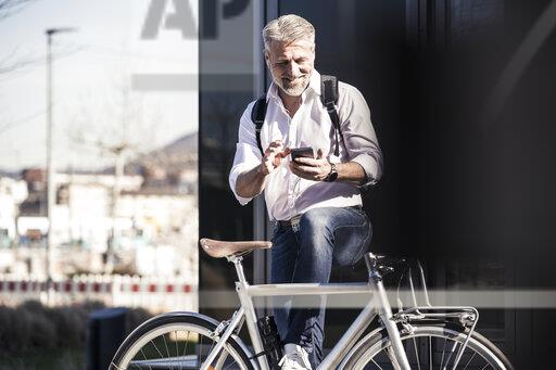 Smiling mature businessman with bicycle and earphones using cell phone