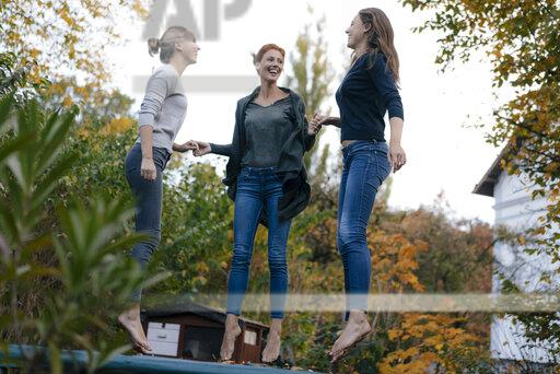 Happy mother with two teenage girls jumping on trampoline in garden in autumn