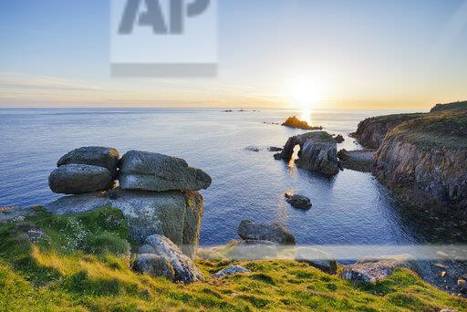United Kingdom, England, Cornwall, Land's End, Natural Arche and Armed Knight at sunset
