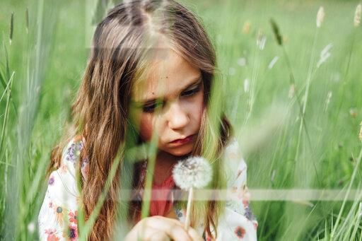 Portrait of unhappy girl looking at blowball on a meadow