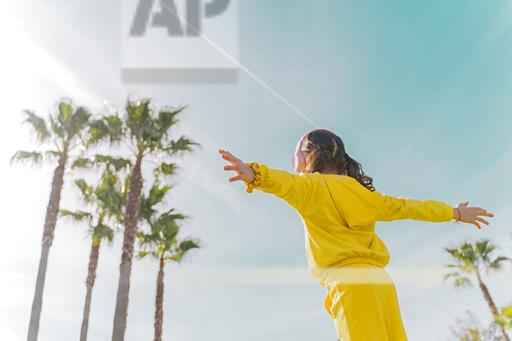 Back view of little girl with arms outstretched listening music with headphones outdoors