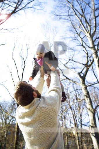 Father lifting up happy daughter in park