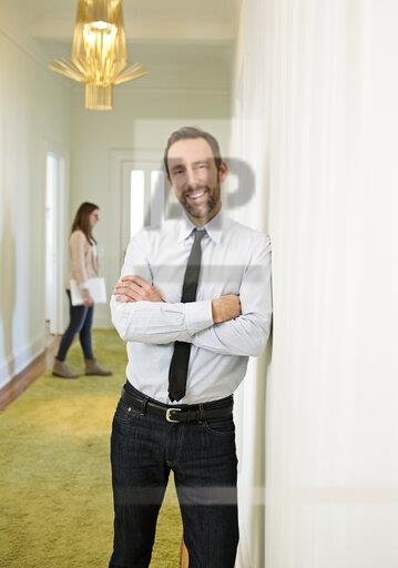 Portrait of smiling businessman leaning against the wall on office floor