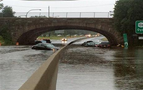 Vehicles are submerged on a flooded section of the Northern State Parkway, near Route 107, in Jericho, N.Y., on New York's Long Island, Wednesday Aug. 13, 2014. Stranded Long Island drivers have been rescued after a storm slammed Islip, N.Y., with over 12 inches of rain — an entire summer's worth. (AP Photo/Newsday, Howard Schnapp) NYC LOCALS OUT