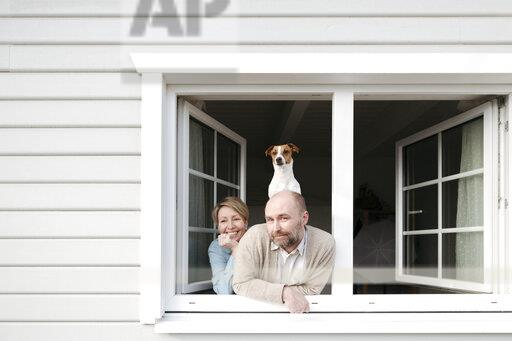 Couple with dog leaning out of window of their house
