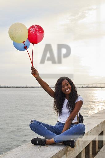 Mocambique, Maputo, portrait of happy young woman with three balloons sitting in front of the sea