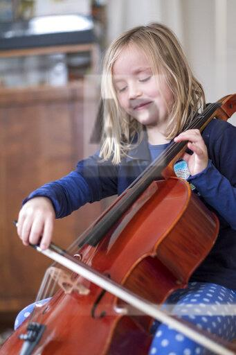 Portrait of smiling blond girl playing cello
