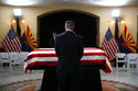 A guest pays their respects at the casket of Sen. John McCain, R-Ariz. during a memorial service at the Arizona Capitol on Wednesday, Aug. 29, 2018, in Phoenix. (AP Photo/Jae C. Hong, Pool)
