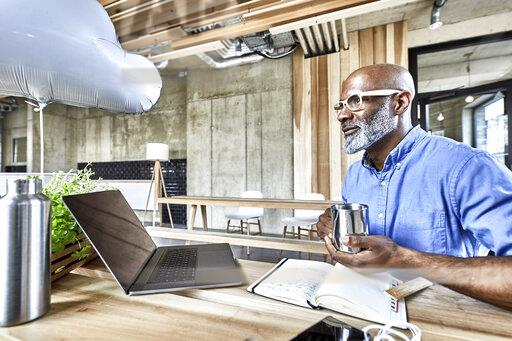 Mature businessman sitting at table in modern office with cloud balloon and laptop
