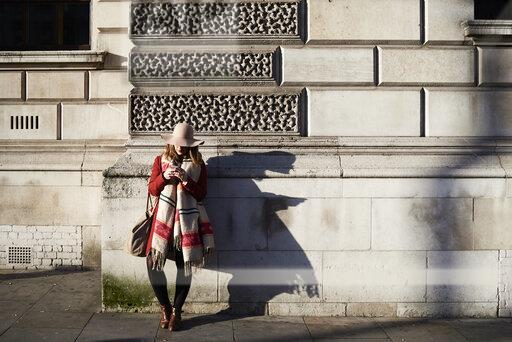 Stylish woman standing at a building using cell phone