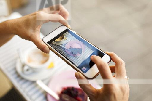 Female hands taking a picture of piece of cake with smartphone