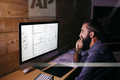 Young architect working hard on a new project at home at night