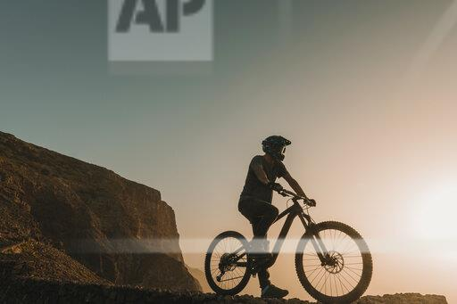 Spain, Lanzarote, mountainbiker on a trip at sunset